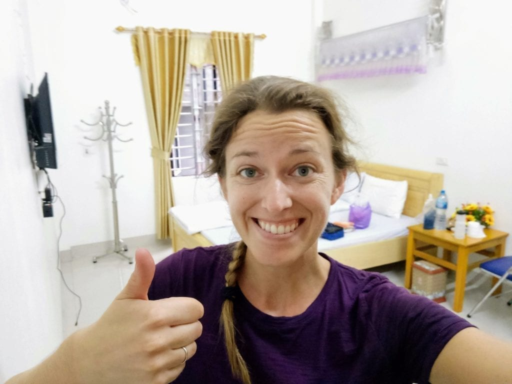 Happy cyclist in clean guesthouse room