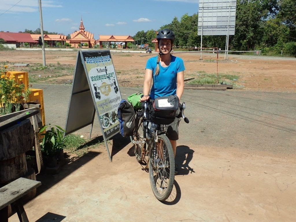 Woman with touring bicycle at Cambodian border