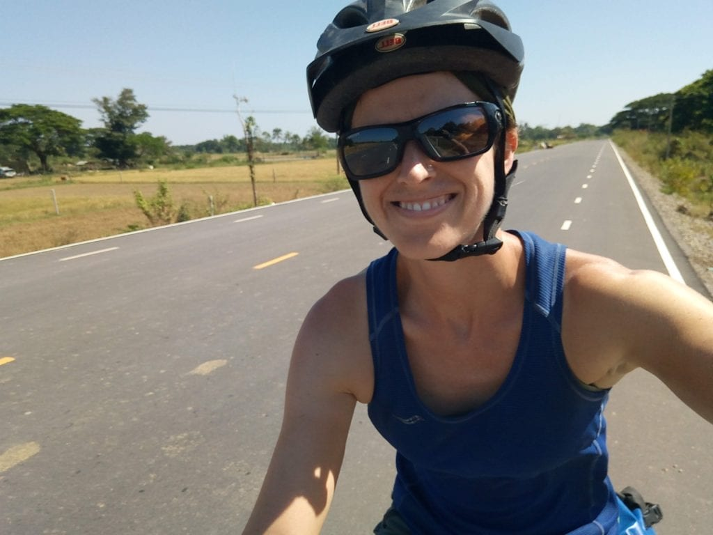 Experimenting with a sleeveless shirt - and enjoying an unusually lovely stretch of smooth wide road in Laos!