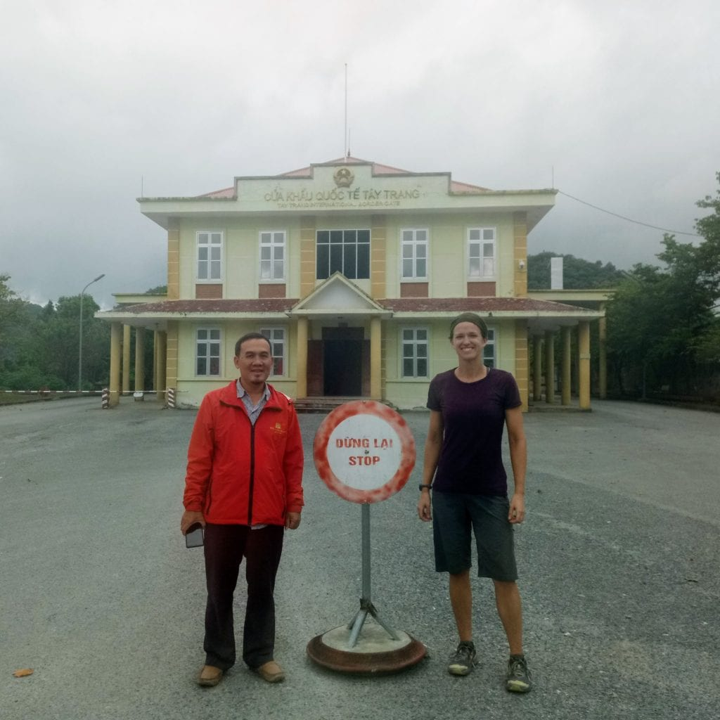 Standing with Vietnamese friend in front of border post