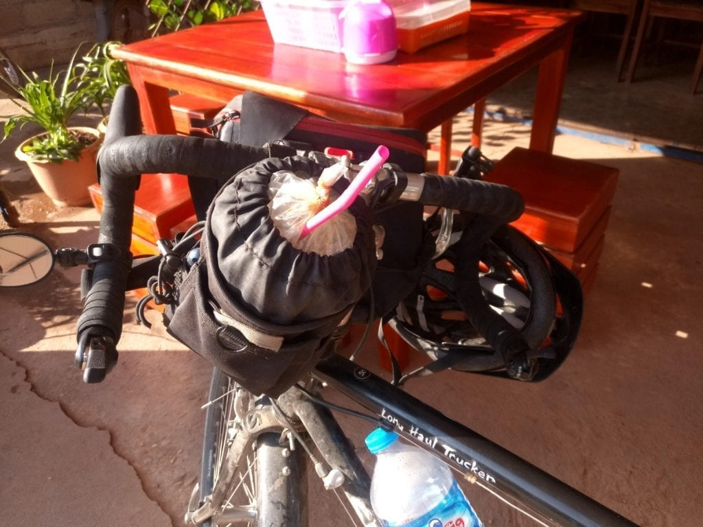 Bicycle handlebar bag holding iced coffee