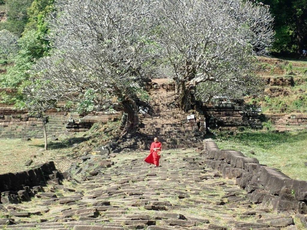 Monk in red robe on ruined walkway of Wat Phu, Laos