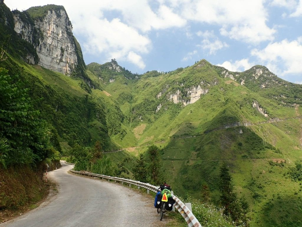 Touring bicycle leaning against guardrail on mountainous road in northern Vietnam