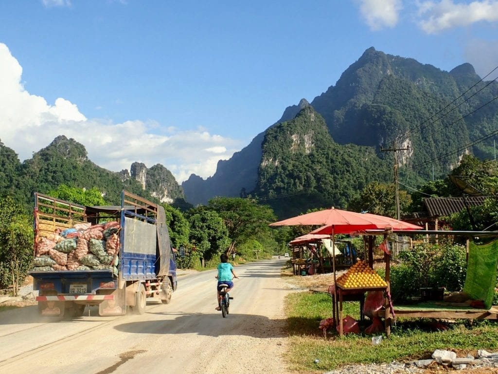 Truck and boy on bicycle on small road in Laos mountains