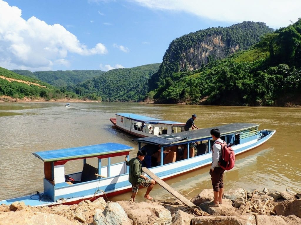 Two wooden boats on river in Laos with mountains in the distance