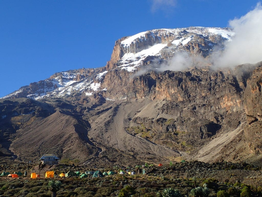 A tent camp with Kilimanjaro summit behind