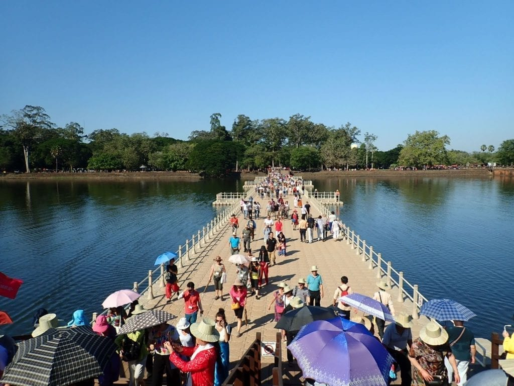 Crowds of tourists crossing bridge to Angkor Wat