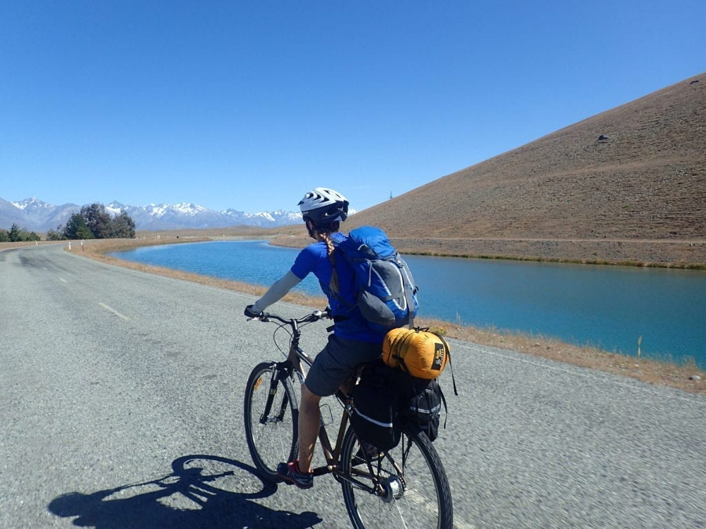 Bicycle touring on path next to aqueduct on Alps to Ocean trail in New Zealand
