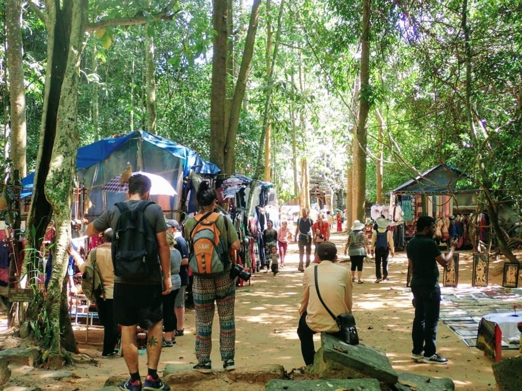 Tourists walking through small market at Angkor Wat temple complex