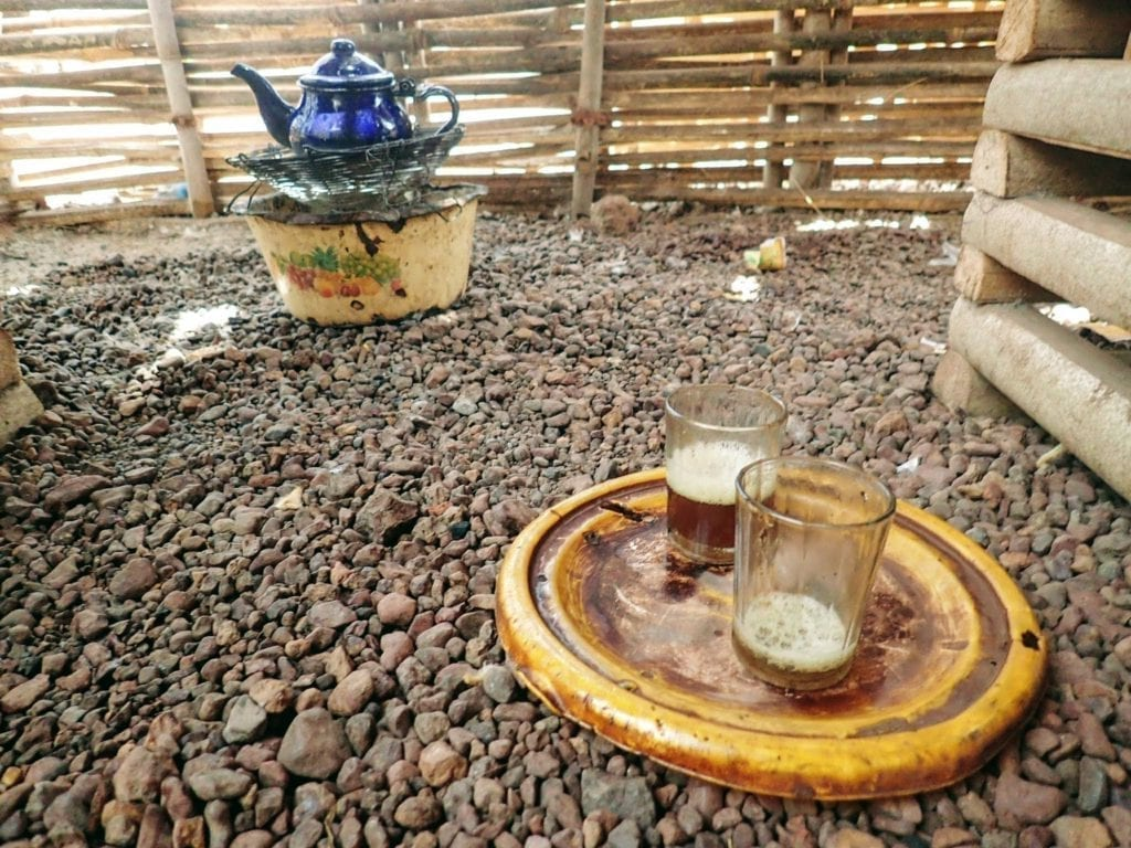 Two small glasses of Senegalese tea rest on a metal lid on the rocky ground, with a blue teapot in the background.