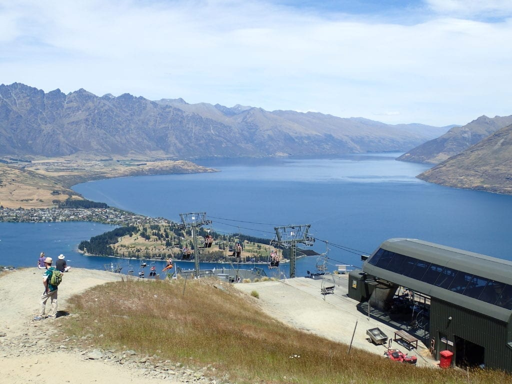 Chairlift and view of lake and mountains from top of hill near Queenstown