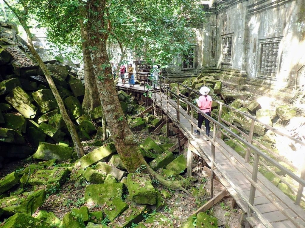 Wooden walkway allows tourists to walk through Beng Mealea temple ruins in Cambodia