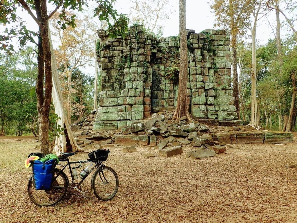 Touring bicycle parked in front of temple ruins in Koh Ker, Cambodia
