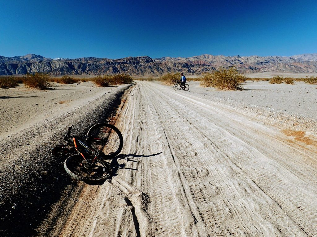Two mountain bikers on sandy desert road in Death Valley