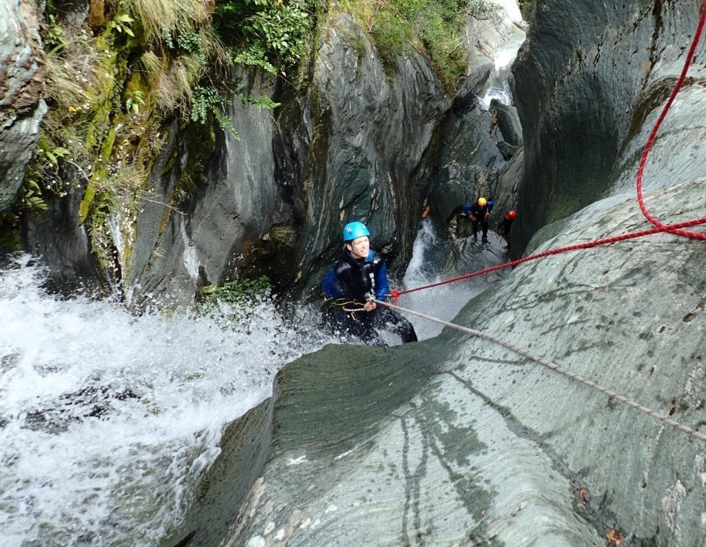 Rappelling down a waterfall while canyoning in New Zealand