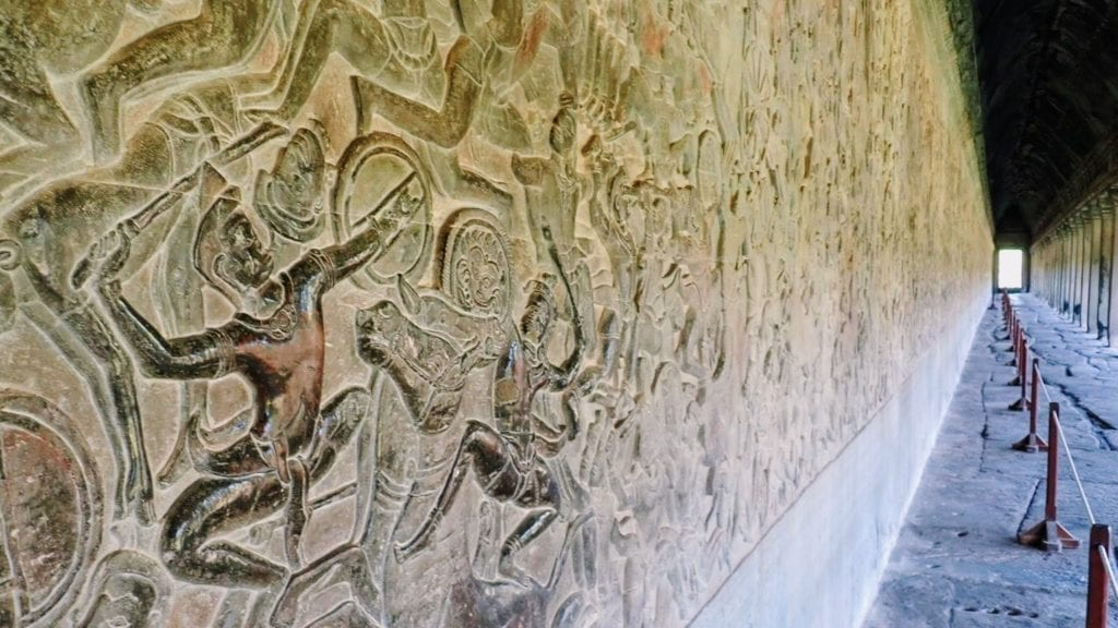 Intricate stone carvings of a battle scene on the walls of Angkor Wat.