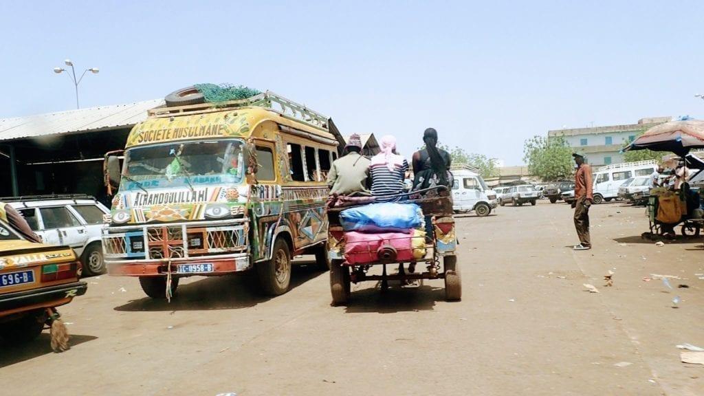 Colorful minibus and cart at taxi park in Kedougou, Senegal