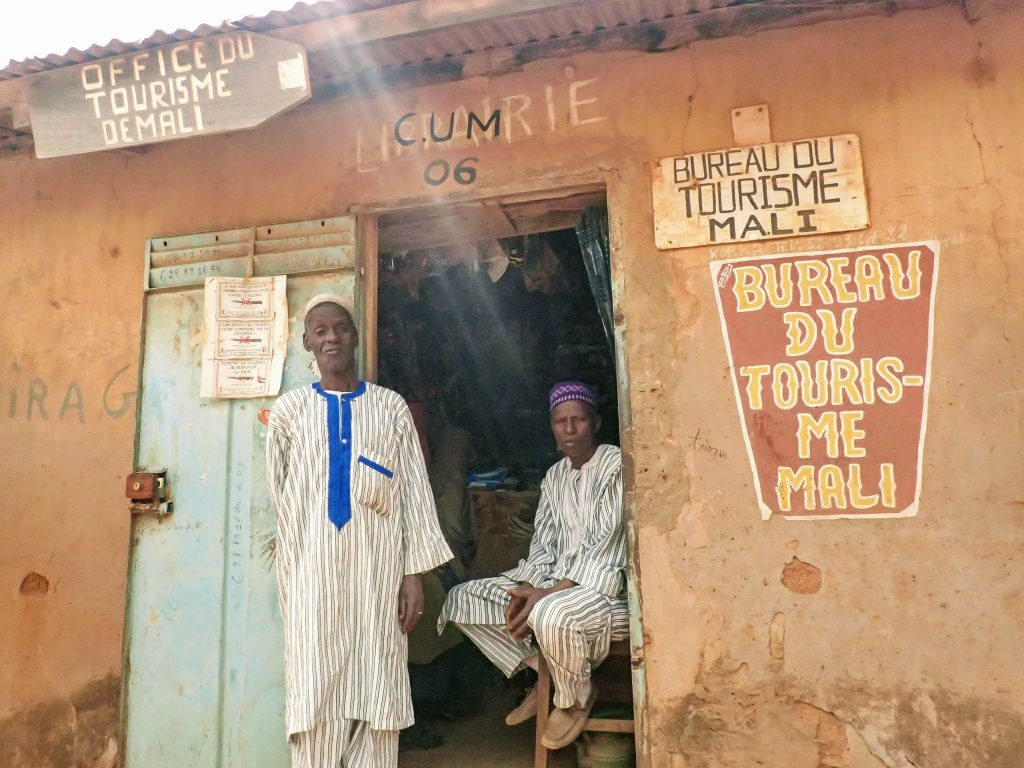 "Two Guinean men stand outside a ramshackle office labeled ""Bureau du Tourisme Mali"""