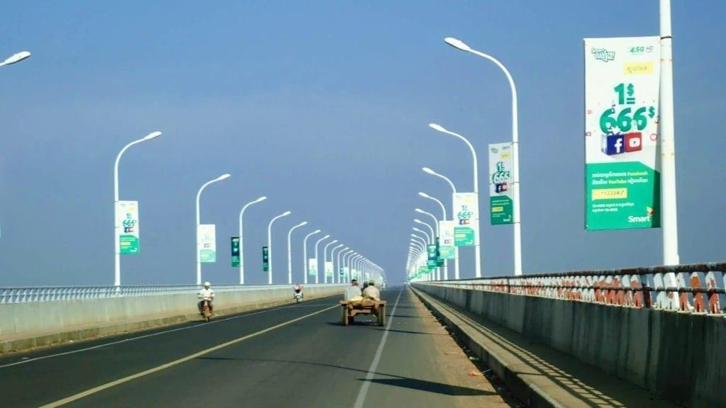 Small cart crosses modern bridge over Mekong River in Cambodia