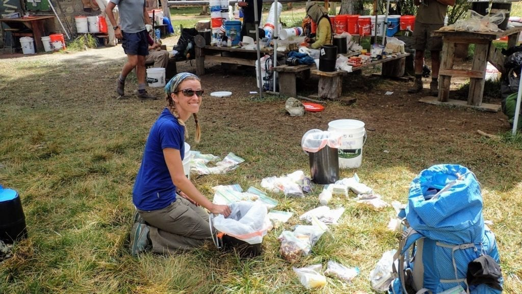 A hiker sorts food on the lawn at Muir Trail Ranch