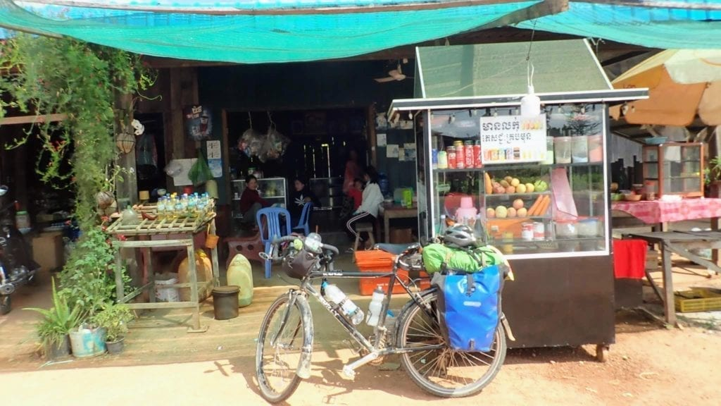 Touring bicycle parked at rural roadside restaurant in Cambodia