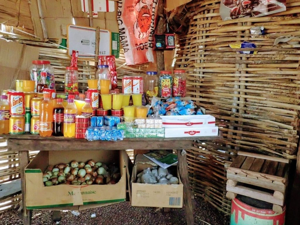 Table displaying basic drinks and snacks in a woven hut in a Guinean village