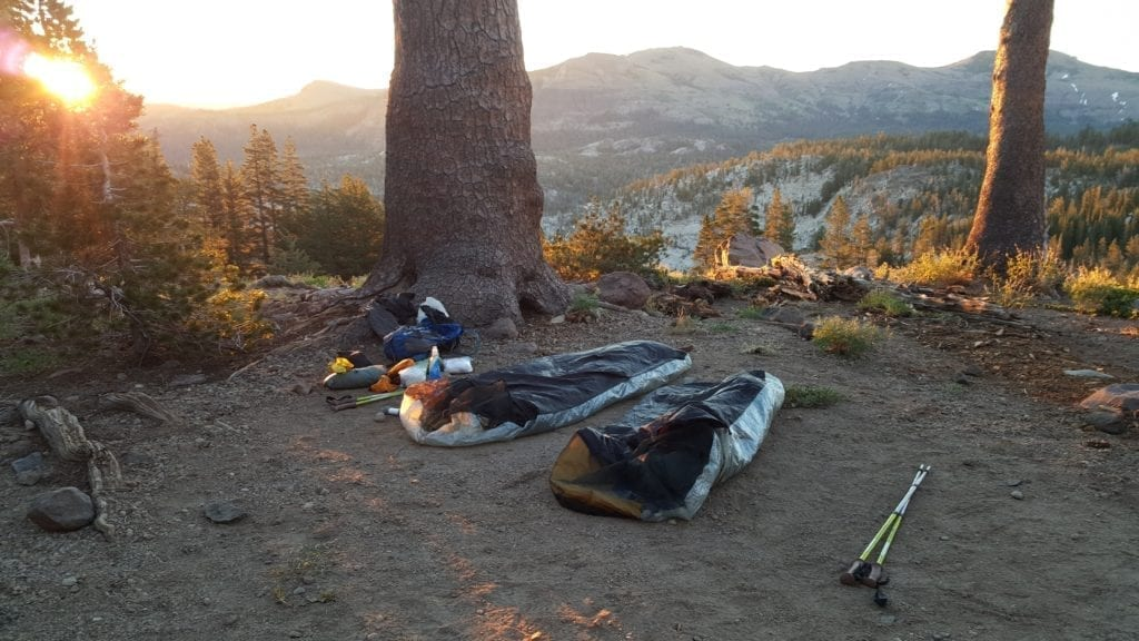 Two bivy sacks at mountain campsite at sunrise