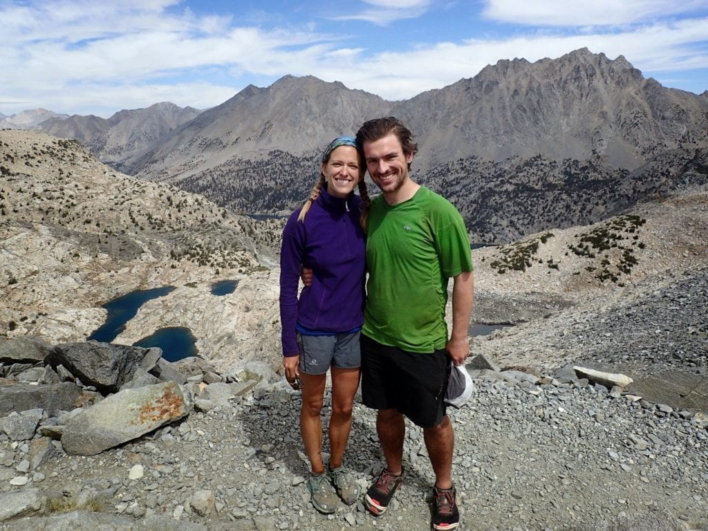 A couple stands together at Glen Pass with granite mountains and alpine lakes in the distance