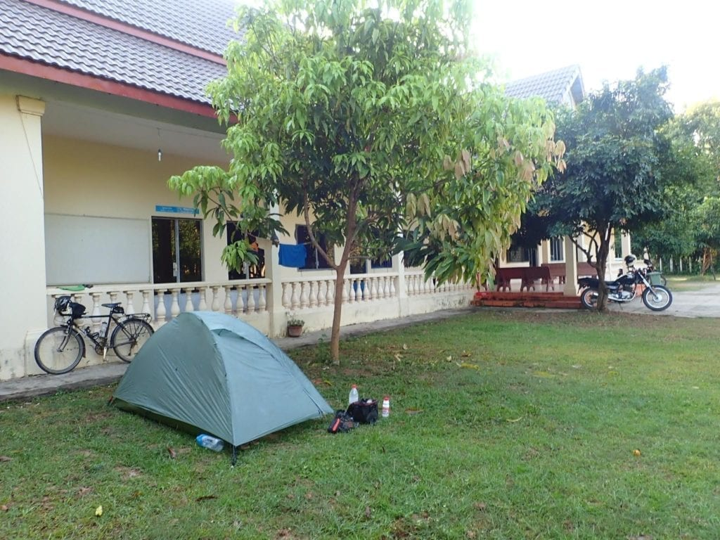 Tent and touring bicycle on front lawn of tourist police station in Siem Reap