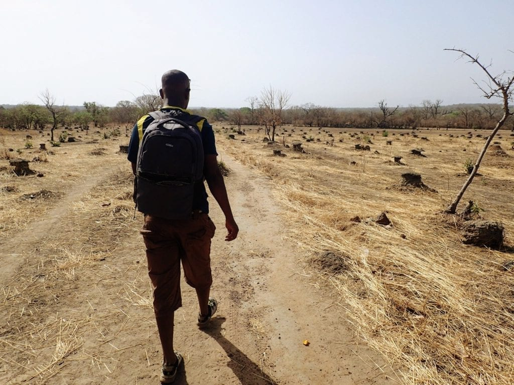Following a guide across dry grassland in Senegal