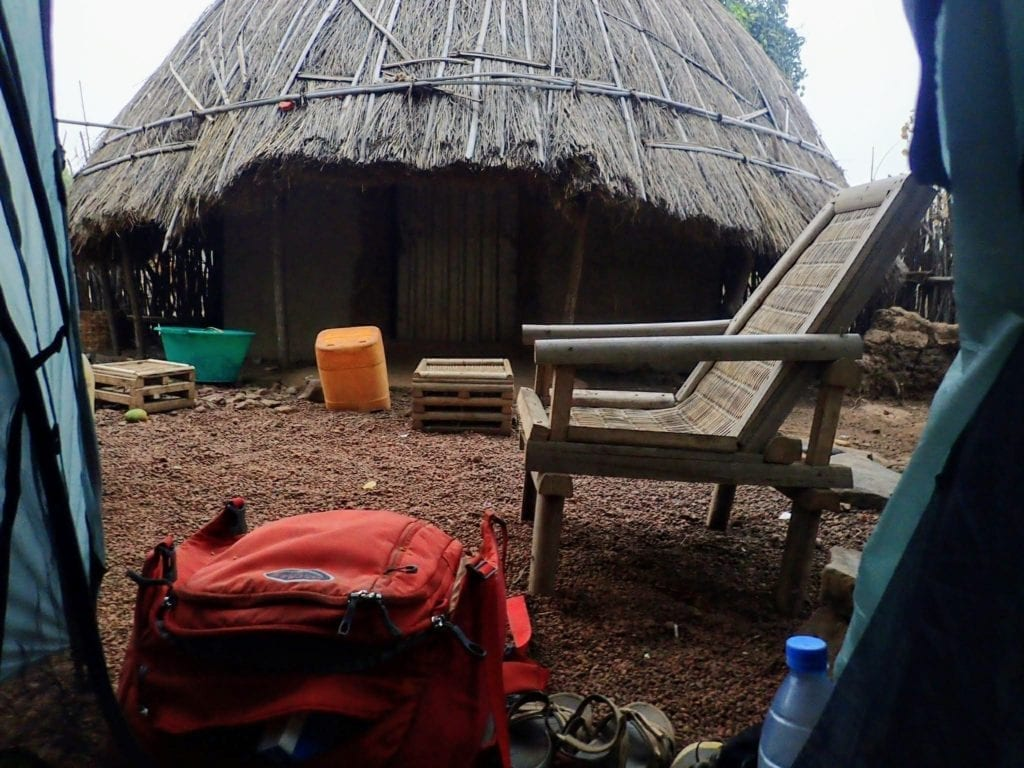 View out tent door of a thatched hut and woven furniture.