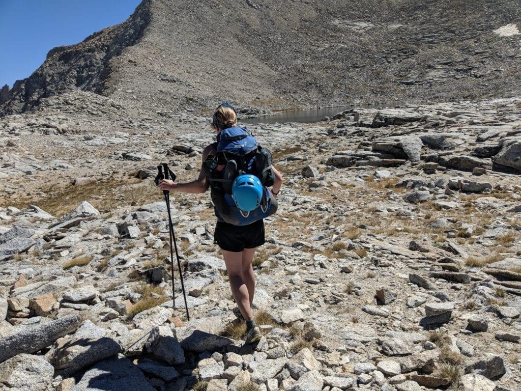 Backpacker crossing rocky terrain in high Sierra