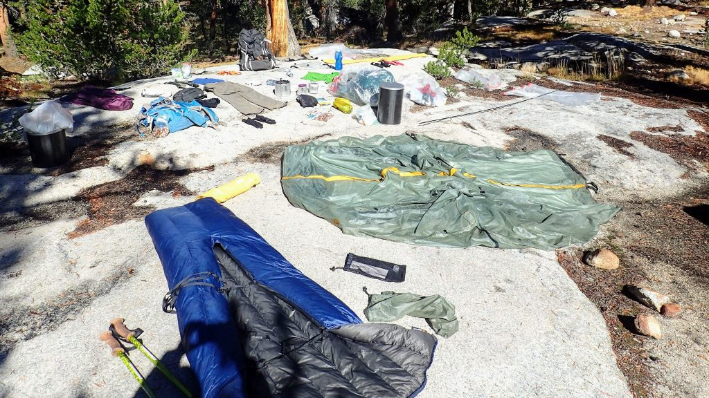 Backpacking gear drying on rock after rain