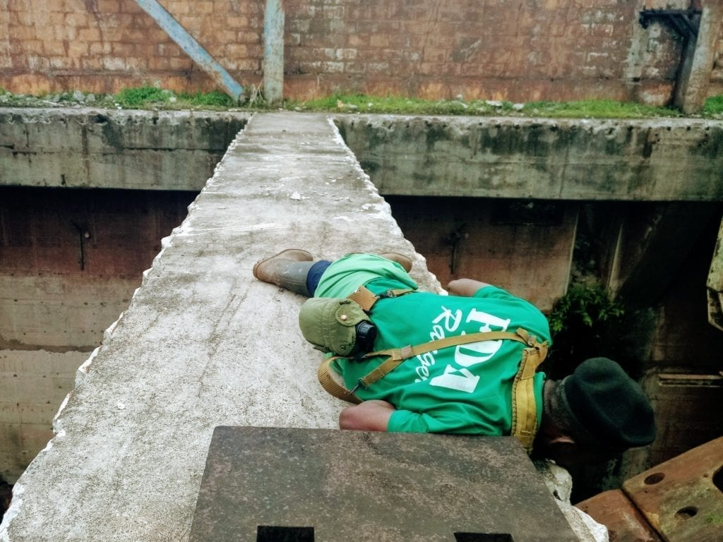 Guide lies flat on concrete beam and looks down into pit