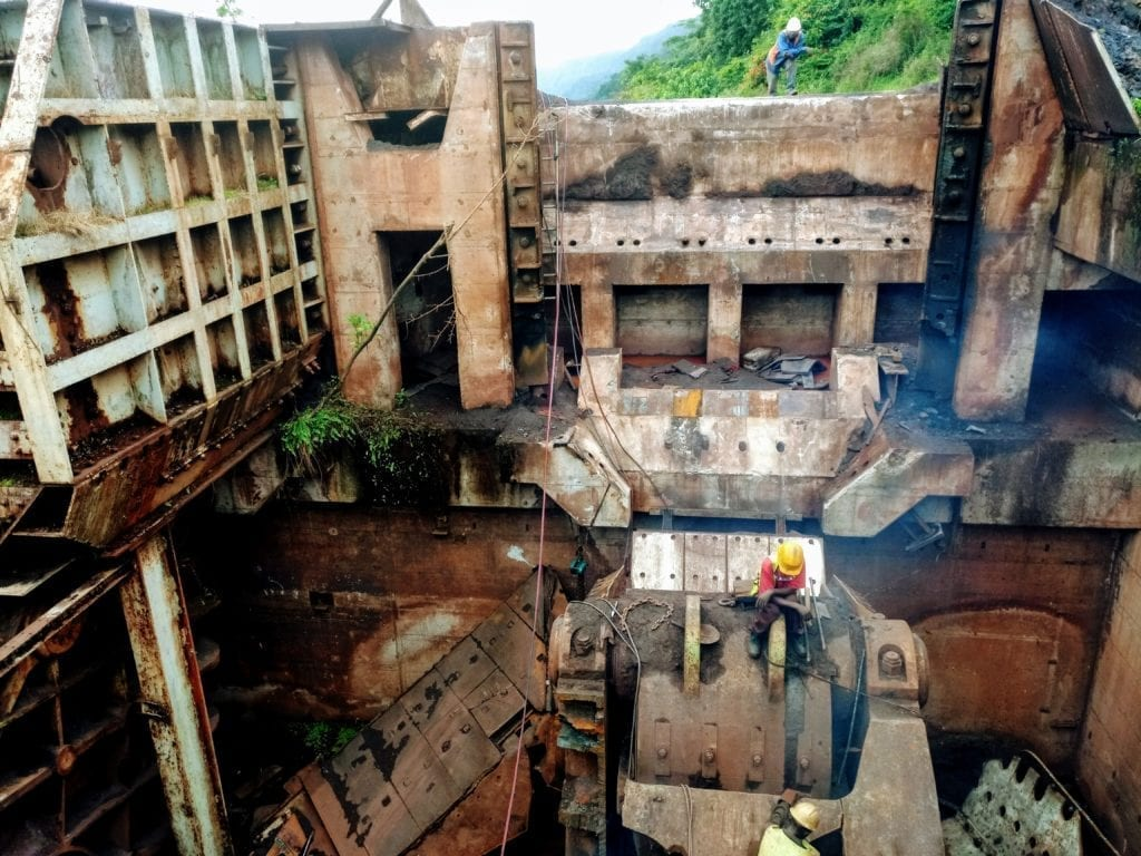 Workers cut apart old mining equipment to sell as scrap on Mount Nimba
