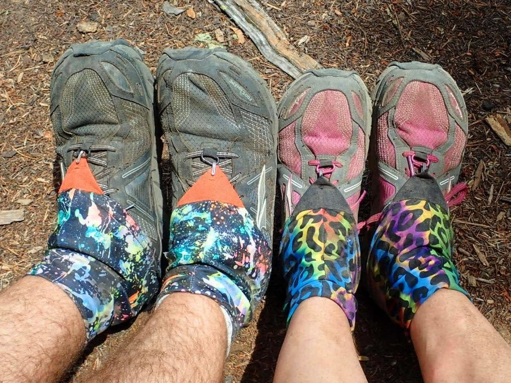 Two pairs of feet in trail running shoes and colorful gaiters