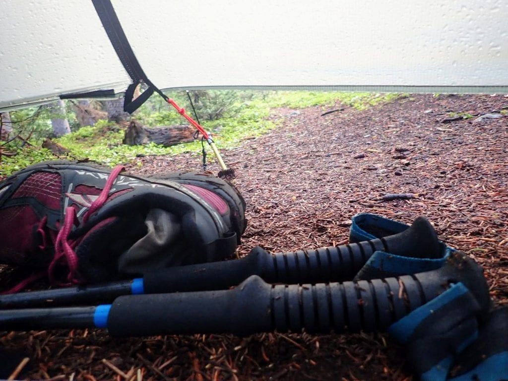 Trail running shoes and hiking poles under tarp