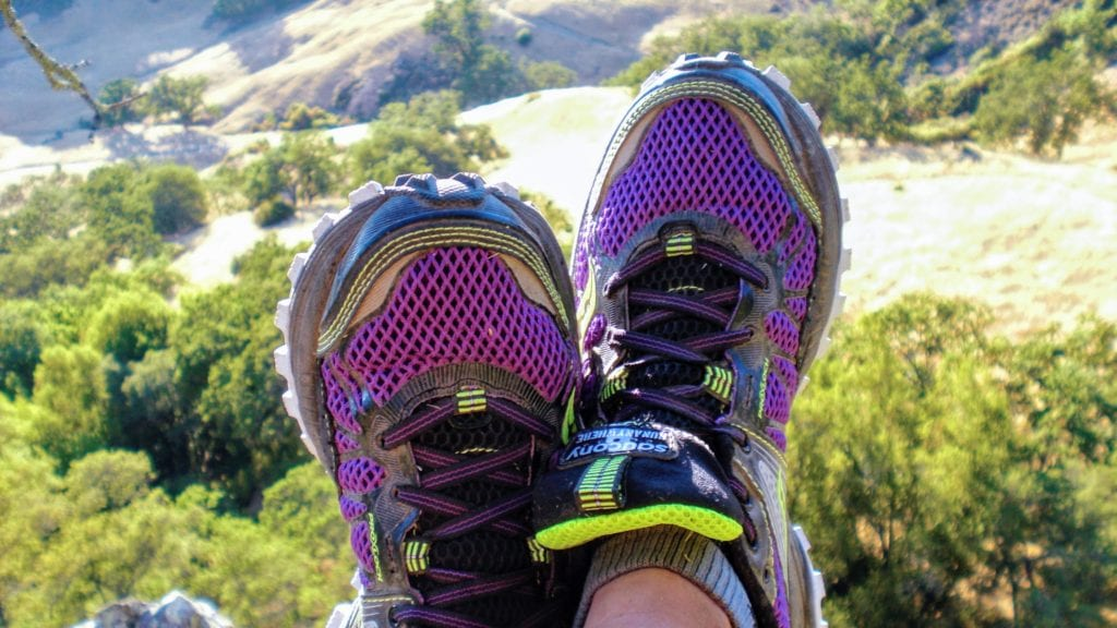 Purple trail running shoes with view of hills in background