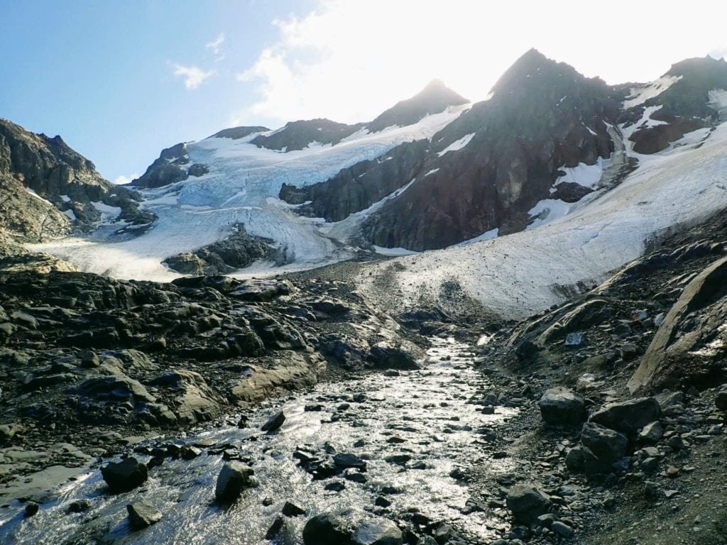 Vinciguerra Glacier with stream running down rocky landscape
