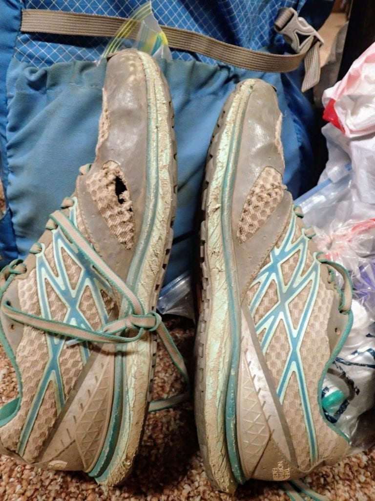 Well used trail running shoes with holes in the side