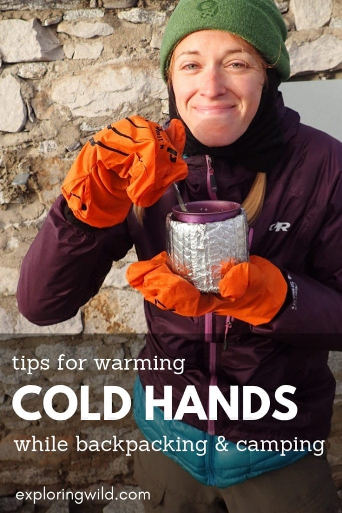 Female hiker eating with mittens on and text overlay: tips for warming cold hands while backpacking and camping