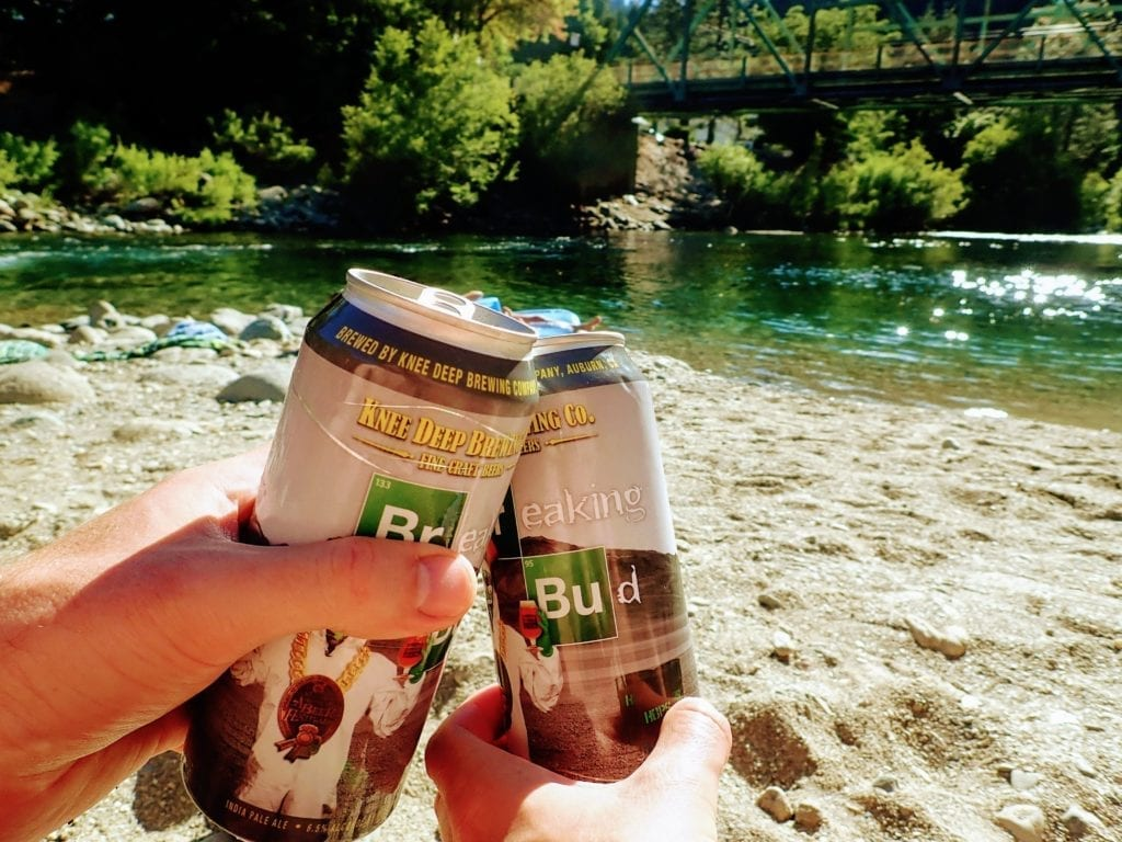 Two beer cans toasting on beach with Downieville river in background