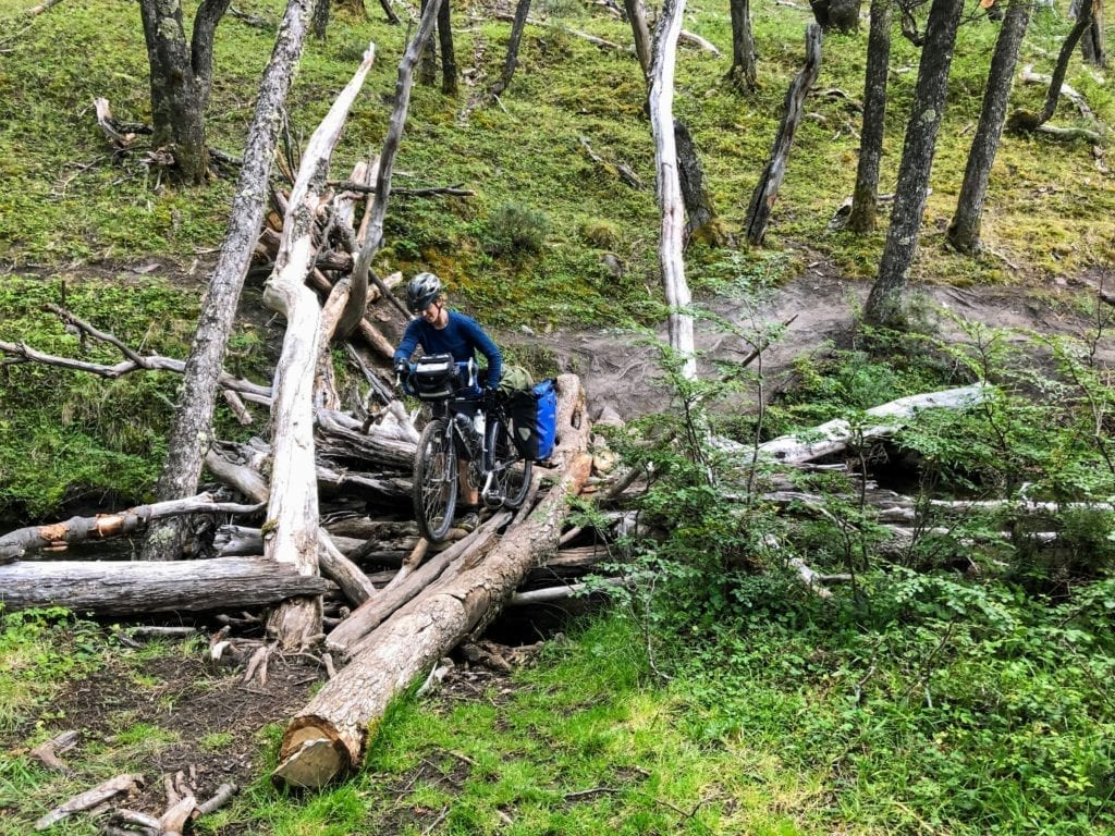 Cyclist pushing loaded touring bike across rickety log bridge
