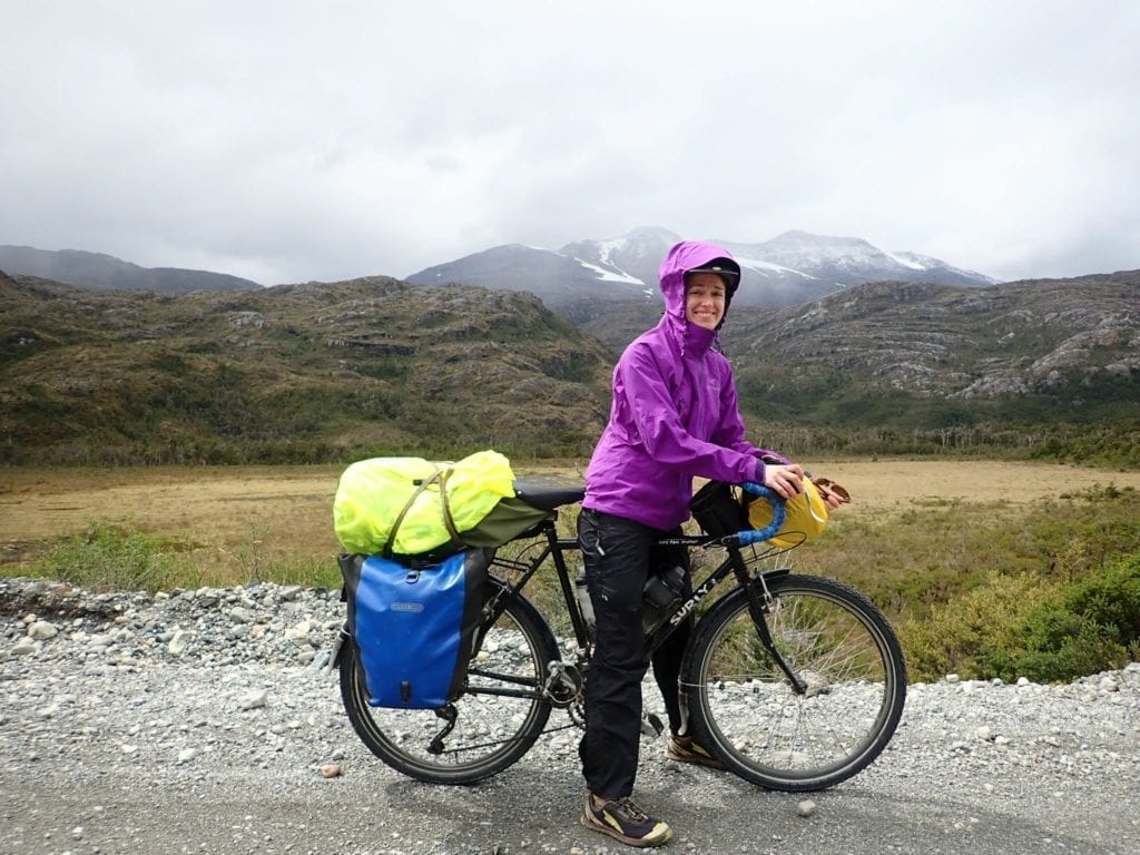 Bicycle traveler in purple Arc'teryx rain jacket on the Carretera Austral in Chile