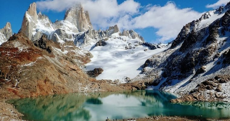 Rocky mountain spires with glacier and bright blue alpine lake