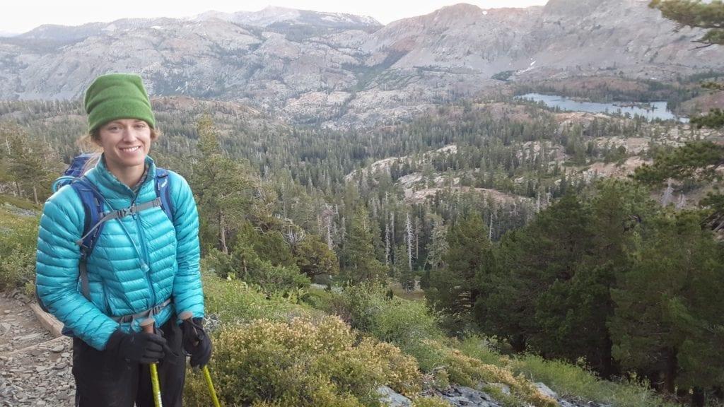Hiker in Mountain Hardwear Ghost Whisperer down jacket in front of valley on Tahoe Rim Trail