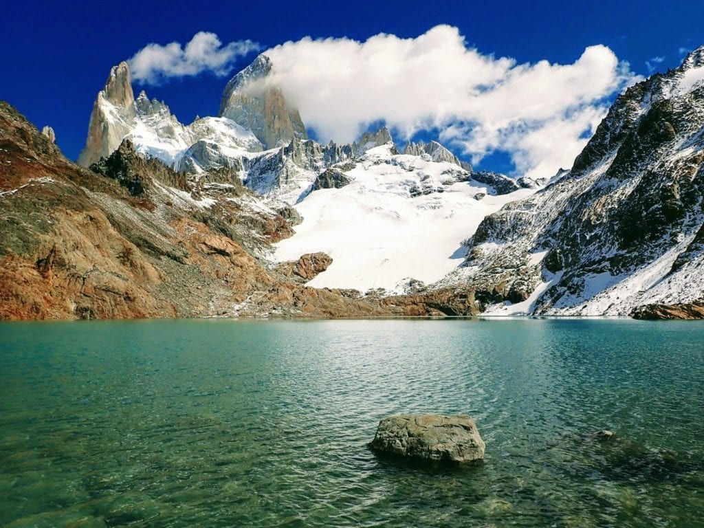 Bright blue mountain lake with glacier and Mount Fitz Roy in background