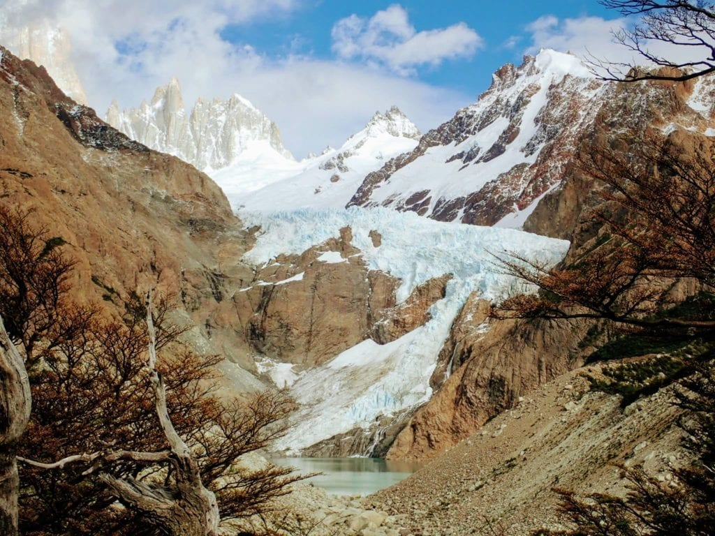 Piedras Blancas glacier in rocky ravine above small alpine lake