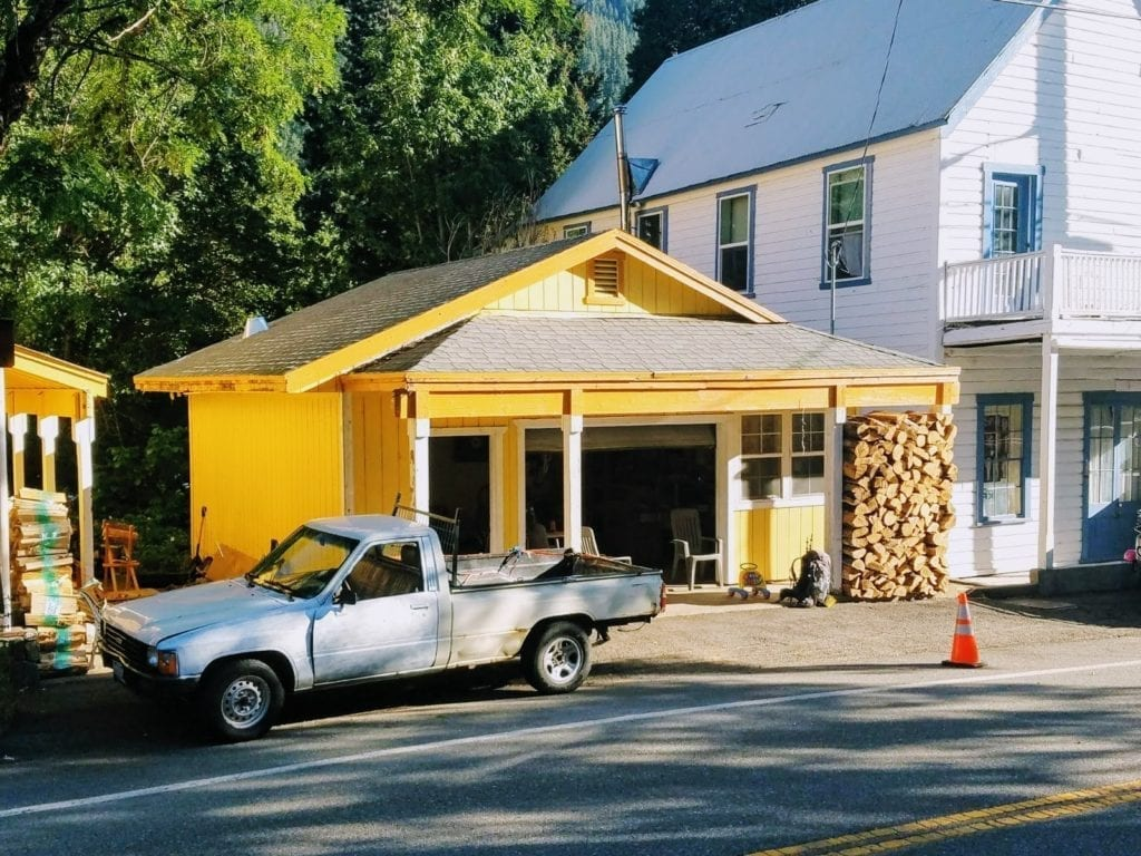 Pickup truck parked next to yellow house with big pile of firewood and hiker's backpack out front