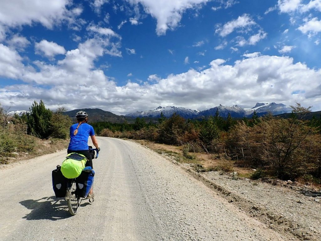 Cycle tourer on sunny gravel road